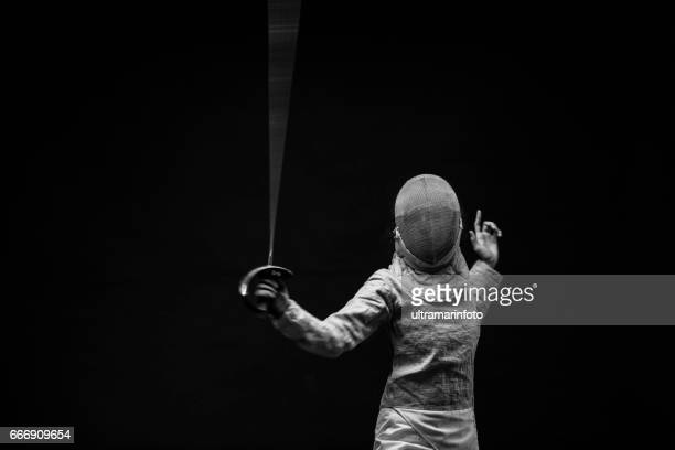 Sporting Women practicing Fencing sport  Women in sport Young woman Fencer action in fencing pose   Black background BW