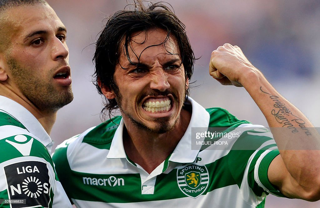 Sporting's Algerian forward Islam Slimani (L) celebrates a goal with teammate Italian defender Ezequiel Schelotto during the Portuguese league football match FC Porto vs Sporting CP at the Dragao stadium in Porto on April 30, 2016. Sporting won the match 3-1. / AFP / MIGUEL