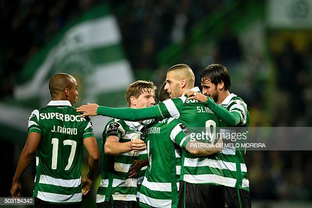 Sporting's Algerian forward Islam Slimani celebrates with his teammates after scoring during the Portuguese League football match Sporting CP vs FC...