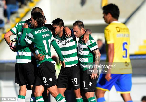 Sporting's Argentinian forward Alan Ruiz celebrates with teammates after scoring a goal during the Portuguese league football match Arouca FC vs...