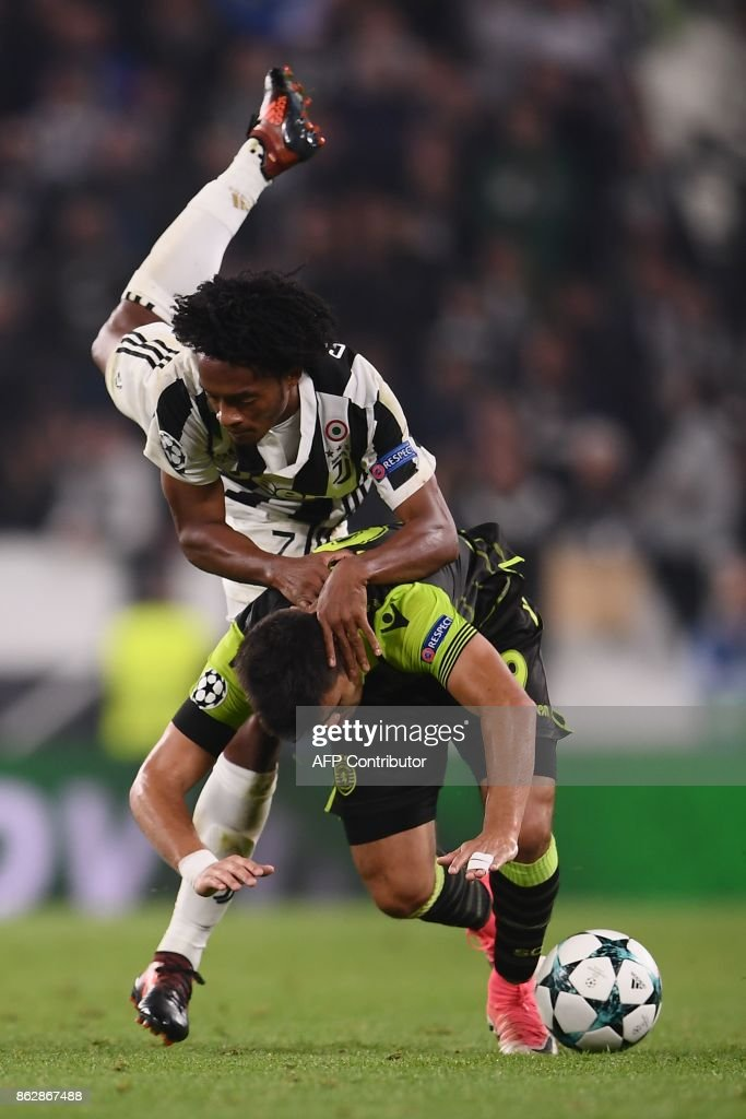 Sporting's Argentinian forward Marcos Acuna (bottom) fights for the ball with Juventus' forward from Colombia Juan Cuadrado during the UEFA Champions League Group D football match Juventus vs Sporting CP at the Juventus stadium on October 17, 2017 in Turin. / AFP PHOTO / Marco BERTORELLO