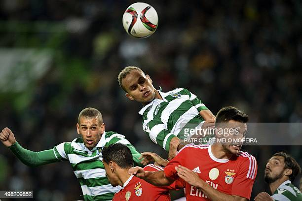 Sporting's Brazilian defender Ewerton and Sporting's Algerian forward Islam Slimani heads the ball with Benfica's Greek midfielder Andreas Samaris...