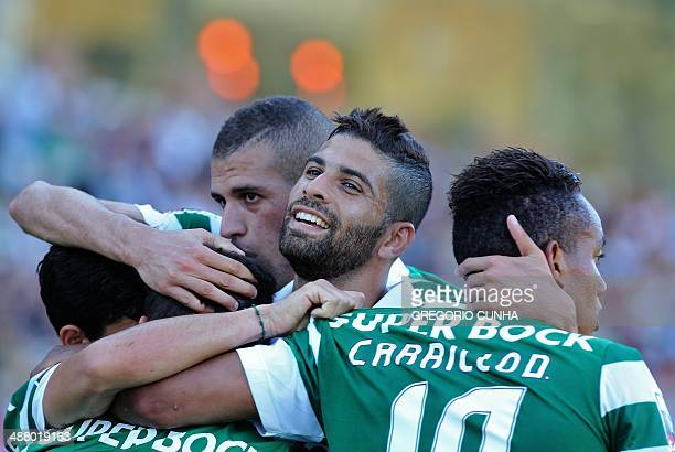 Sporting's Brazilian midfielder Gerson Magrao celebrates with his teammates after Nacional's defender Nuno Campos scored a self goal against Nacional...