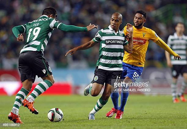 Sporting's Colombian forward Teofilo Gutierrez and teammate midfielder Joao Mario vie with Estoril's Cape Verdean midfielder Babanco during the...
