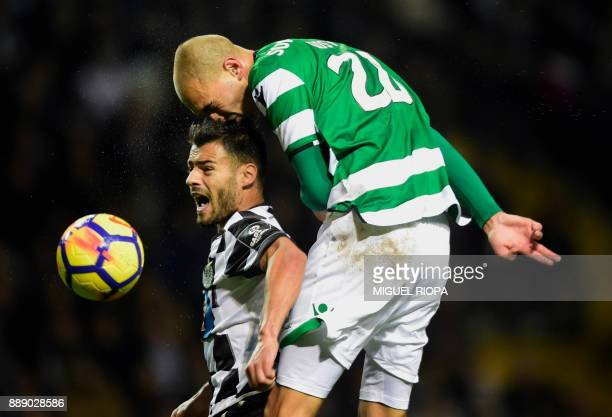 TOPSHOT Sporting's Dutch forward Bas Dost heads the ball next to Boavista's Portuguese midfielder Carraca during the Portuguese league football match...