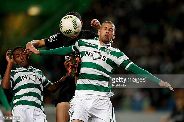 Sporting's forward Islam Slimani heads for the ball with Academica's defender Rafa Soares and Sporting's forward Gelson Martins during the Portuguese...