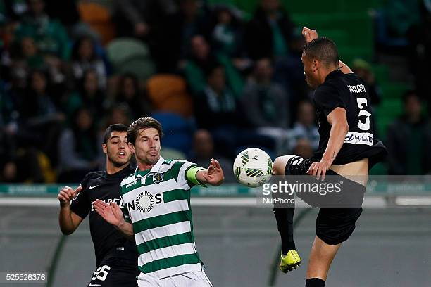 Sporting's midfielder Adrien Silva vies for the ball with Academica's defender Ricardo Nascimento and Academica's defender Rafa Soares during the...