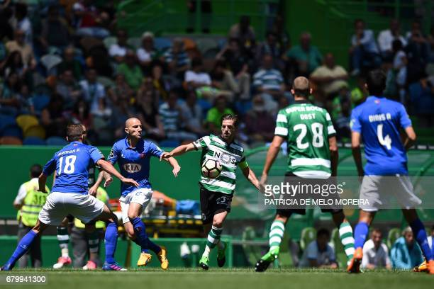 Sporting's midfielder Adrien Silva vies with Belenenses' midfielder Andre Sousa during the Portuguese league football match Sporting CP vs OS...