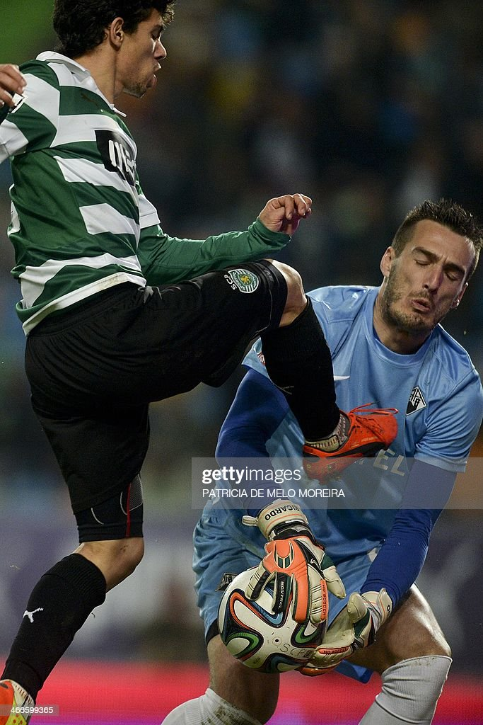 Sporting's midfielder Andre Martins (L) vies with Academica's goalkeeper Ricardo during the Portuguese league football match Sporting vs Academica at the Alvalade stadium on February 2, 2014.