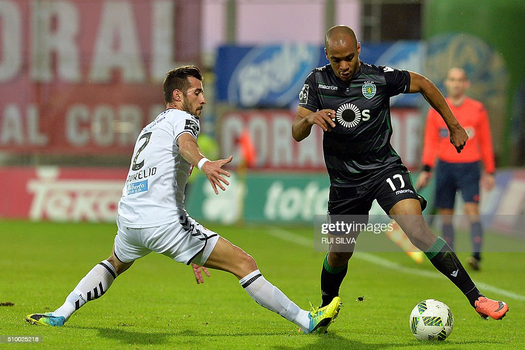 Sporting's midfielder Joao Mario (R) vies with Nacional's defender Joao Aurelio during the Portuguese league football match CD Nacional Funchal vs Sporting CP at the Madeira stadium in Funchal on February 13, 2016. / AFP / RUI SILVA