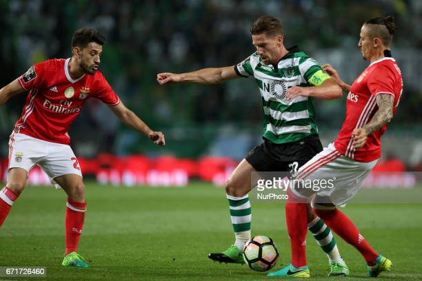 Sporting's Portuguese midfielder Adrien Silva vies with Benfica's Portuguese forward Pizzi and Benfica's Serbian midfielder Ljubomir Fejsa during the...