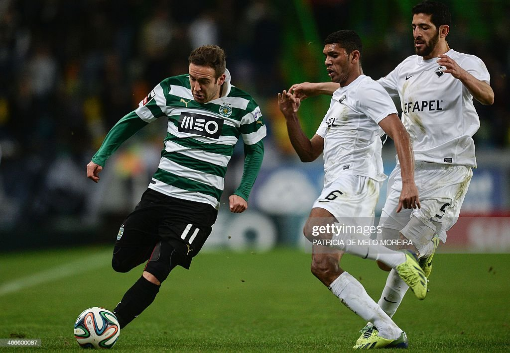 Sporting's Spanish midfielder Diego Capel (L) vies with Academica's Brazilian defender <a gi-track='captionPersonalityLinkClicked' href=/galleries/search?phrase=Djavan+-+Brazilian+Soccer+Player&family=editorial&specificpeople=14921085 ng-click='$event.stopPropagation()'>Djavan</a> (C) and Academica's Algerian defender Halliche during the Portuguese league football match Sporting vs Academica at the Alvalade stadium on February 2, 2014. The game ended in a draw 0-0.