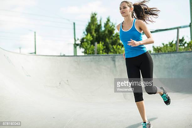 Sportive young woman running in a skate park