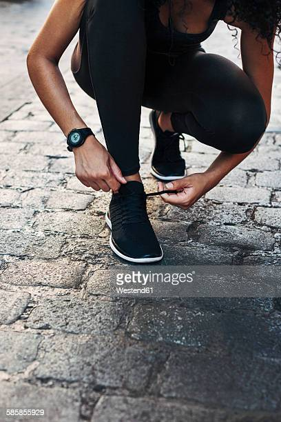 Sportive young woman tying her shoe on pavement