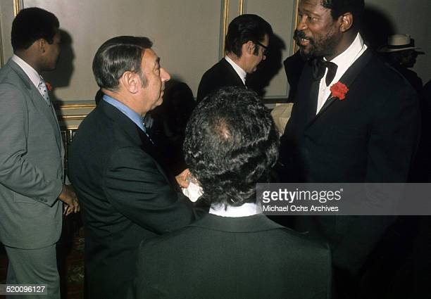 Sports announcer Howard Cosell talks with former NBA player Bill Russell as Muhammad Ali walks behind Cosell circa 1977 in Los Angeles California