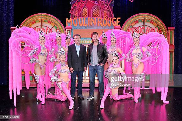 ESPN Sports Broadcaster Chris Fowler and Sports Commentator Jesse Palmer pose backstage with dancers at Le Moulin Rouge on May 29 2015 in Paris France