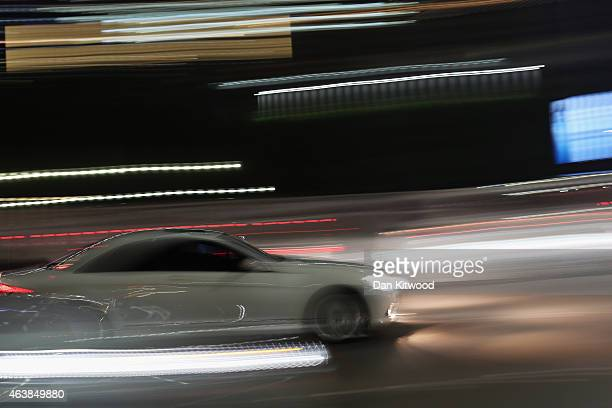 A sports car drives down the Corniche on February 5 2015 in Abu Dhabi United Arab Emirates Abu Dhabi is the capital of the United Arab Emirates and...