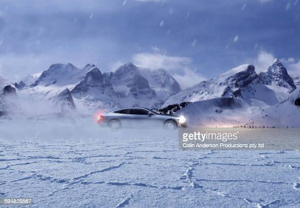 Sports car driving in snowy remote landscape