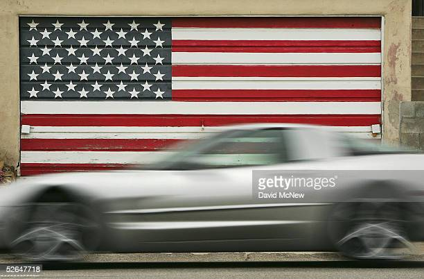 A sports car on the Pacific Coast Highway passes a garage door painted as an American flag near Carbon Beach a public beach that was gotten to...