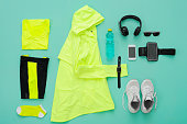Sports clothing and accessories on turquoise background. The concept of a healthy lifestyle. Preparation of sports clothing to training.