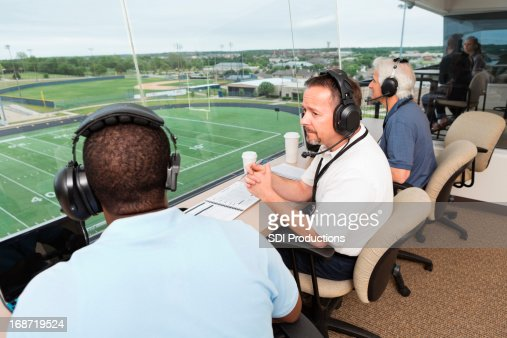 Sports Commentators discussing football game in the press box