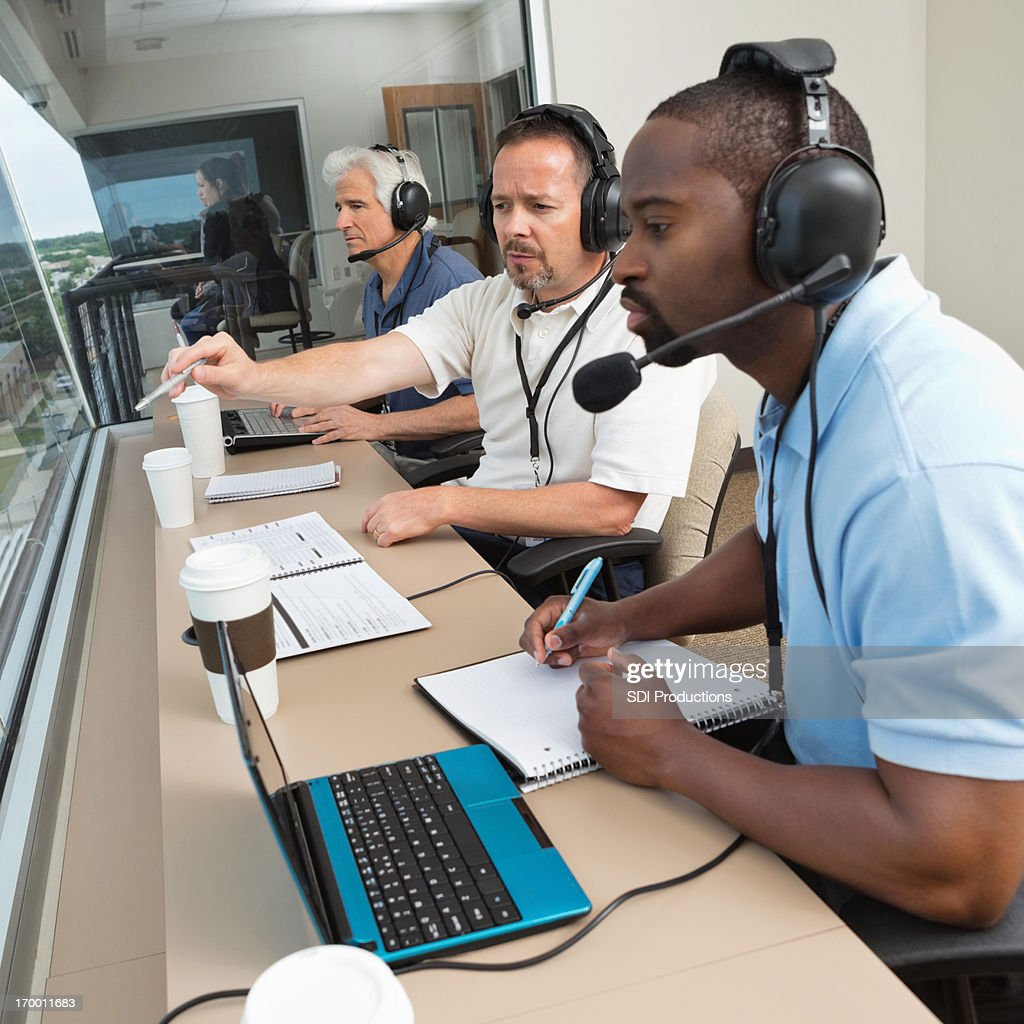 Sports commentators discussing play during game from stadium press box : Stock Photo