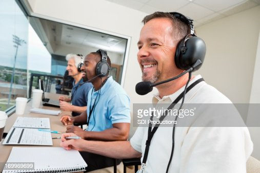 Sports commentators wearing headsets; reporting from stadium press box