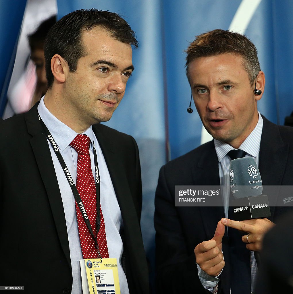 Sports Director of Canal +, Cyril Linette (L) is pictured before the start of the French L1 football match between Paris Saint-Germain and AS Monaco at the Parc des Princes Stadium in Paris on September 22, 2013.