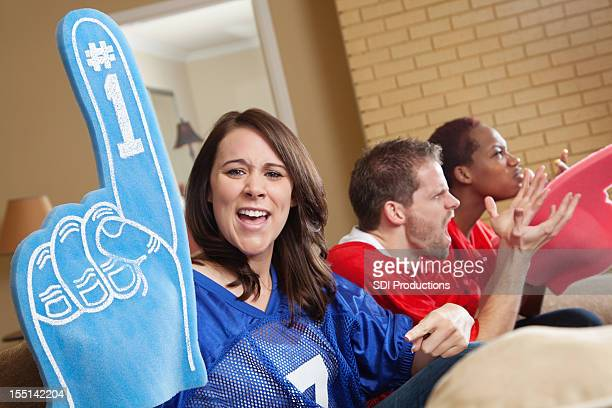 Sports fan at game party holding up foam hand
