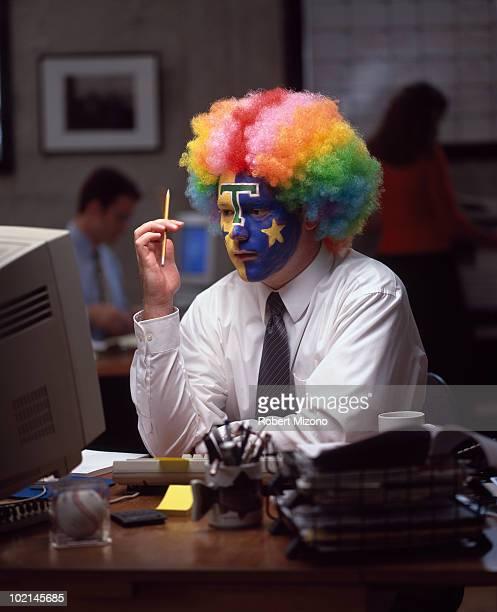 Sports fan wearing clown makeup in office