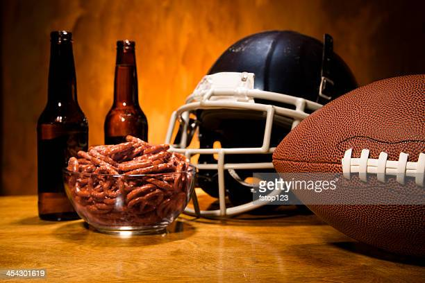 Sports:  Football helmet, ball on table.  Pretzels and beer. Superbowl.