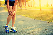 Runner athlete leg  got a pain while jogging at tropical park trail,