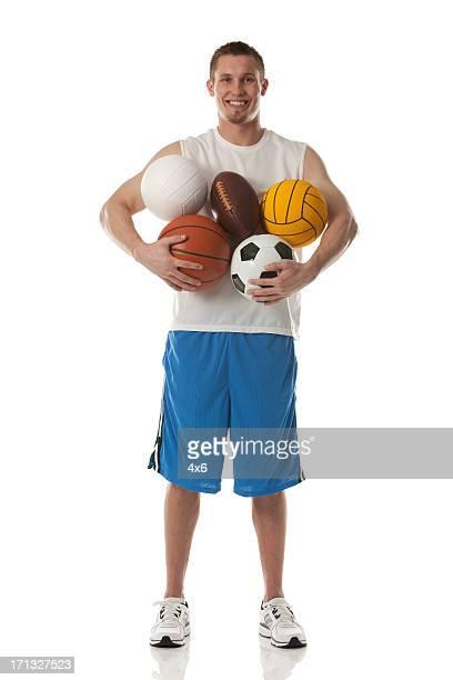 Sports man holding assorted balls