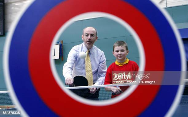 Sports minister Stewart Maxwell and 11yearold David McLoughlin aim at a target on a table tennis table during the launch of 2014 Communities a fund...