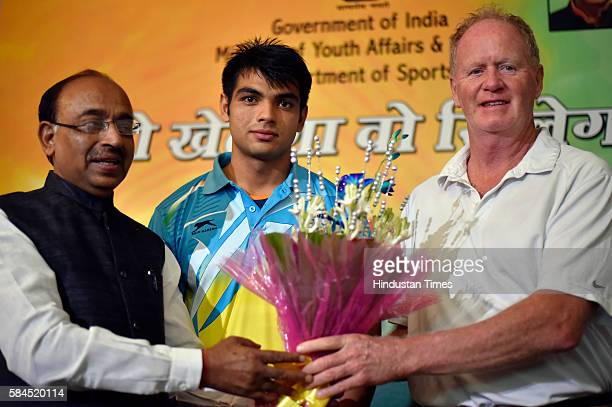 Sports minister Vijay Goel congratulates Javelin thrower Neeraj Chopra and his coach Gary Calvert at his residence on July 27 2016 in New Delhi...