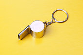 Sports or coaches metal whistle, closeup. Concept refereeing sport on yellow card background. Soccer or football referee whistle and caution cards