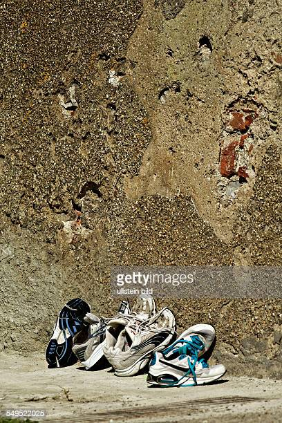 Sports shoes leaning against concrete wall Portoferraio Elba Tuscany Italy