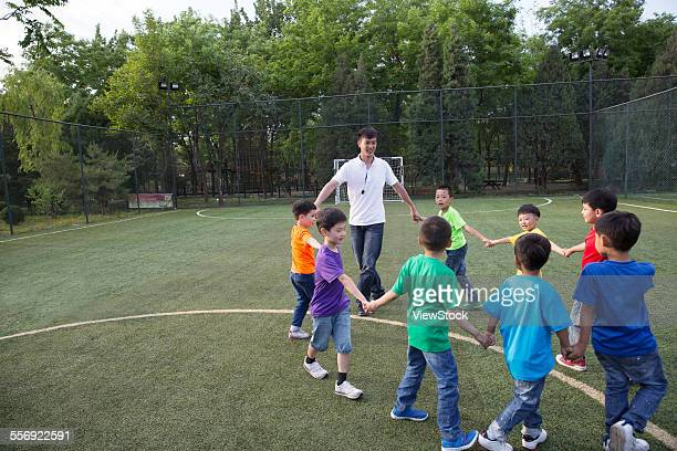 Sports teacher holding the hand of the children play games on the sports field