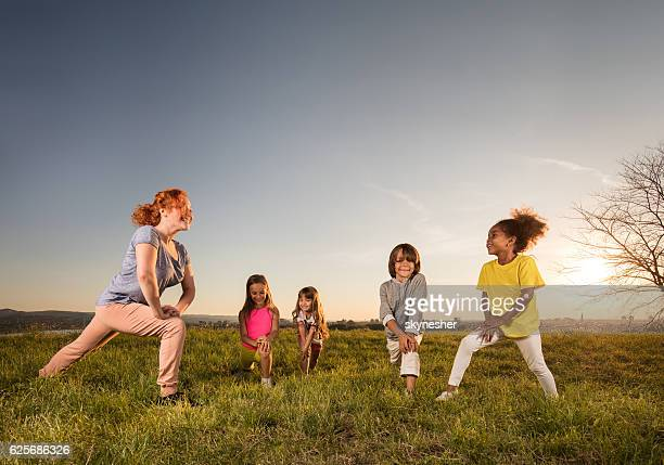 Sports trainer exercising with group of kids at sunset.