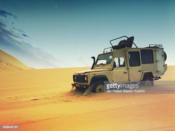 Sports Utility Vehicle On Desert Against Sky