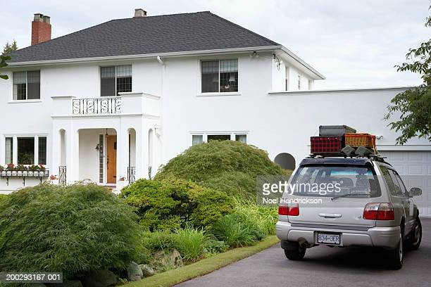 Sports utility vehicle parked in front drive of house, loaded with luggage