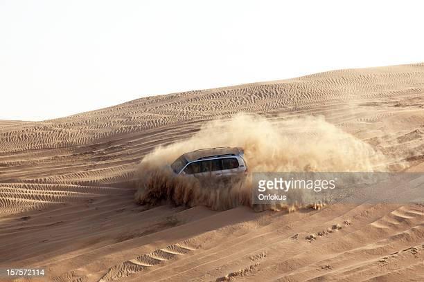 Sports Utility Vehicle speeding in desert sand, Dubai, UAE