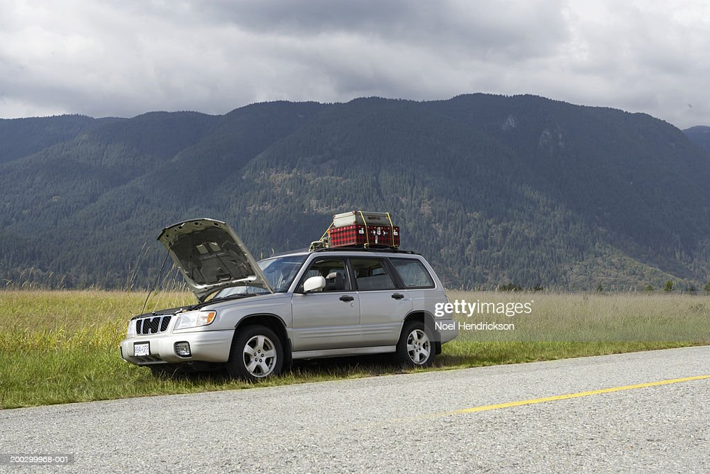 Sports utility vehicle with bonnet open parked beside rural road