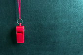 Sports whistle on a red lace.Concept- sport competition, referee, statistics, challenge, friendly match.Copy space.