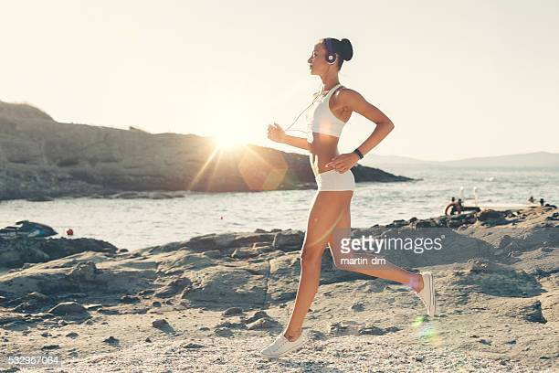 Sports woman jogging at the beach