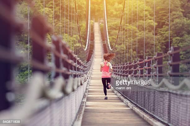 Sportliche Frau Joggen auf der Brücke
