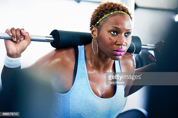 Sports woman lifting weights at the gym