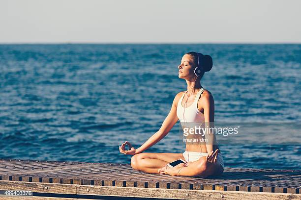 Sports woman meditating at the quay