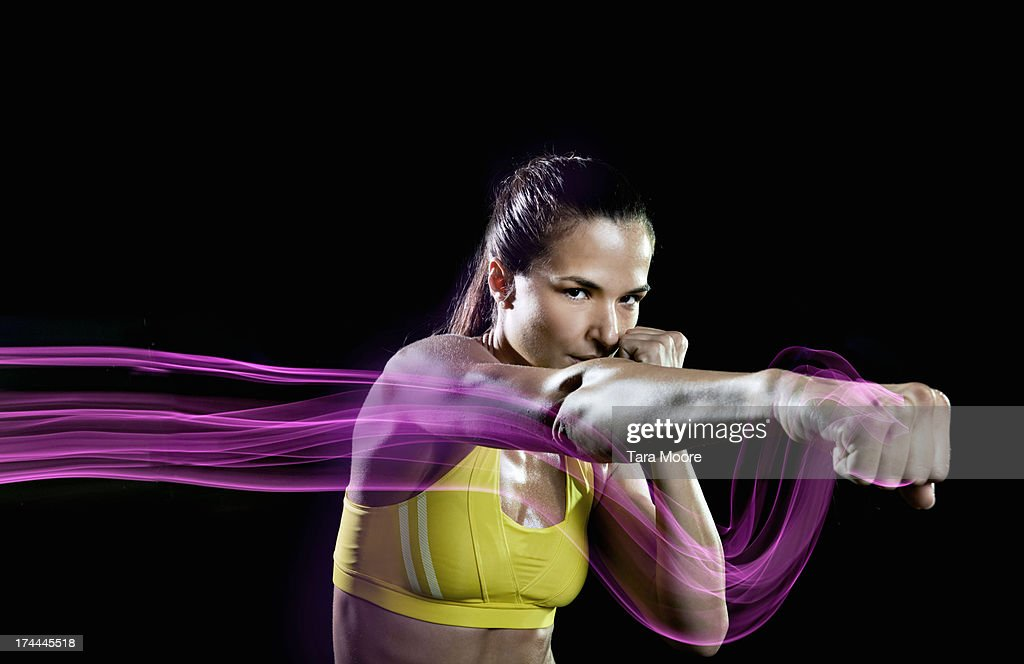 sports woman punching air with light trails : Stock Photo