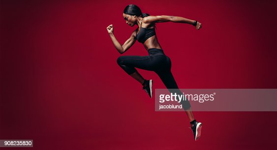 Sports woman running over red background : Foto de stock